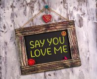 Say you love me written on Vintage sign board. Say you love me written on Vintage wooden sign board hanging on color white wood with heart and flower and smile royalty free stock photo