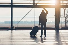 Saying goodbye at the airport. Silhouette of the traveler waves his hand royalty free stock photo