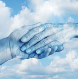 Saying Goodbye. Mourning and grief concept with the hand of a young person letting go an elderly senior who is in the final stages of life on a sky background Stock Photography