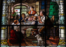 Saying grace - family dinner. Stained glass window created by F. Zettler (1878-1911) at the German Church (St. Gertrude's church) in Gamla Stan, Stockholm Stock Image