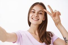 Saying hi to internet followers. Charming friendly-looking joyful girl with brown hair smiling broadly showing peace or royalty free stock image