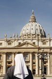 Saying a Prayer. A Nun prays in St Peter's Basillica in Vatican City. Rome. We see the back of the nun in her habit and the Dome of St Peter royalty free stock photography