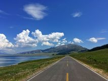 Road by Sayram Sailimu Lake Blue sky. Sayram Lake Sàilǐmù hú is located in the Bortala Prefecture near the Tian Shan Mountains, Xinjiang, China. In royalty free stock photos