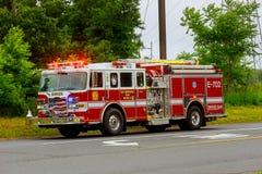 Sayreville NJ USA - Jujy 02, 2018: Firetrucken som kör på en blinkande blått för väg, tänder en skadad bil för olycka royaltyfri foto