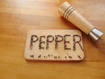 Sazone con pimienta escrito en tabla de cortar con pimienta mientras que el peppermill miente al lado de él Fotografía de archivo libre de regalías