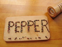 Sazone con pimienta escrito en tabla de cortar mientras que el peppermill miente al lado de él Fotos de archivo libres de regalías