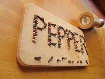 Sazone con pimienta escrito en tabla de cortar mientras que el peppermill miente al lado de él Foto de archivo libre de regalías