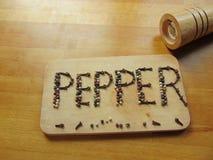 Sazone con pimienta escrito en tabla de cortar mientras que el peppermill miente al lado de él Fotos de archivo