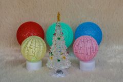 Sazone el fondo del saludo - árbol de navidad ligero con las bombillas de la bola colorida Imagen de archivo
