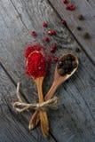 Sazone la mezcla con pimienta en las cucharas de madera en la tabla rústica, especias indias coloridas Imagenes de archivo