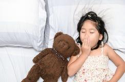 Sbadiglio e sonno della bambina sul letto Fotografia Stock