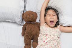 Sbadiglio e sonno della bambina sul letto Fotografie Stock