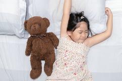 Sbadiglio e sonno della ragazza sul letto con la bambola dell'orsacchiotto Fotografia Stock