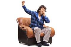 Sbadiglio sonnolento del tipo messo su una poltrona Immagini Stock