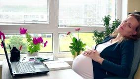 Sbadiglio stanco della donna incinta che si trova nella sedia vicino al computer archivi video