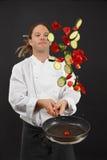 Sballottamento delle verdure mentre cucinando Fotografia Stock