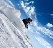 Sbalzo dello sciatore in nubi della polvere della neve Immagini Stock