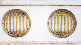 Sbarra di ferro dell'oro con le finestre del cerchio sulla parete bianca rotta fotografia stock