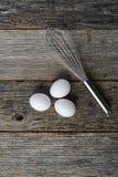 Sbatti e tre uova bianche Immagini Stock Libere da Diritti