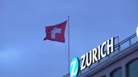 Sbattimento svizzero sopra la costruzione a Zurigo, viaggio della bandiera nazionale in Svizzera stock footage