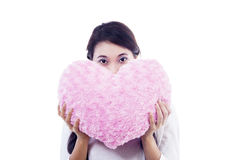 Sbirciata della ragazza tramite il cuscino del cuore Immagine Stock