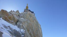 Sbirciata di Aiguille du Midi in alpi nell'inverno con cielo blu Immagine Stock