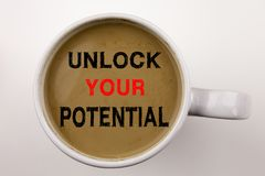 Sblocchi il vostro testo potenziale di scrittura in caffè in tazza Concetto di affari per miglioramento di autosviluppo su fondo  fotografie stock