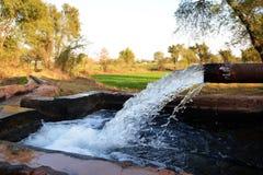Sbocco di un pozzo artesiano ad un bacino idrico temporaneo in un piccolo villaggio del Pakistan Fotografia Stock Libera da Diritti