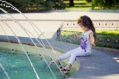 Scène étonnante de peu de fille d'enfant de bébé de mode jouant l'heure d'été avec la fontaine par les jambes aux pieds nus minus Photos stock