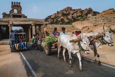 Scène classique de l'Inde avec le sort de personnes sur une voiture et une vache photo stock