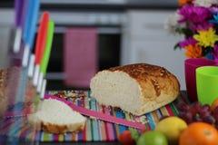 Scène colorée de cuisine avec du pain frais coupé en tranches sur un verrat de coupe Photo stock
