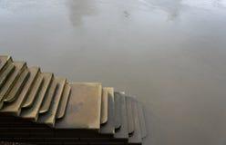 Scène déprimée des étapes menant vers le bas dans l'eau sinistre photos libres de droits