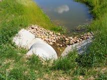 Scène d'écoulement d'eau de rivière de forêt Canalisation de fossé de tuyau Herbe verte Pipe concrète Construction moderne images stock