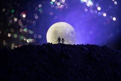 Scène d'amour étonnante Silhouettes de jeunes couples romantiques se tenant sous la lumière de lune illustration stock