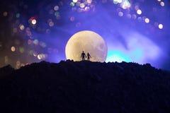 Scène d'amour étonnante Silhouettes de jeunes couples romantiques se tenant sous la lumière de lune Photos libres de droits