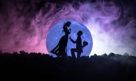 Scène d'amour étonnante Silhouettes de l'homme faisant la proposition à la femme ou silhouettes des couples contre la grande lune Photos libres de droits