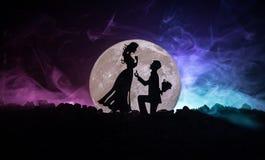 Scène d'amour étonnante Silhouettes de l'homme faisant la proposition à la femme ou silhouettes des couples contre la grande lune Image stock