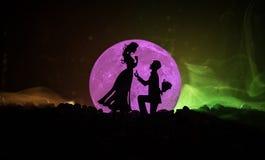 Scène d'amour étonnante Silhouettes de l'homme faisant la proposition à la femme ou silhouettes des couples contre la grande lune Photo stock