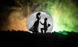 Scène d'amour étonnante Silhouettes de l'homme faisant la proposition à la femme ou silhouettes des couples contre la grande lune Images stock