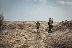 Scène de chasse avec des chasseurs des hommes avec des fusils de chasse explorant la zone rurale pendant la saison de chasse image libre de droits
