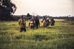 Scène de chasse avec le groupe de chasseurs des hommes passant par l'herbe grande sur le champ rural au coucher du soleil pendant photographie stock
