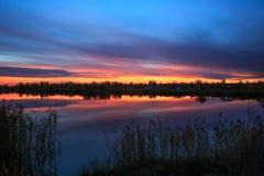 Scène de coucher du soleil au-dessus de la surface de l'eau de lac Photographie stock libre de droits