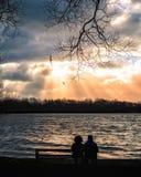 Scène de coucher du soleil avec deux personnes sur un banc en hiver image libre de droits