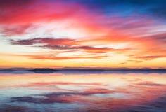 Scène de coucher du soleil sur la mer tranquille avec des montagnes à l'arrière-plan Image stock