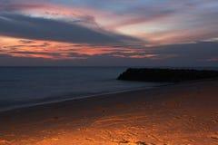 Scène de coucher du soleil sur la plage avec le faisceau lumineux sur le ciel Images stock