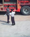 Scène de deux travailleurs devant un camion de la livraison de Coc-kola Photo libre de droits
