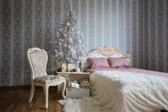 Scène de Noël avec un lit, l'arbre de Noël, les cadeaux et une chaise image libre de droits