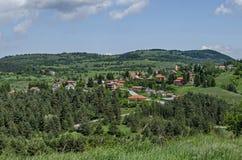 Scène de printemps avec la clairière de montagne, la forêt et le secteur résidentiel du village bulgare Plana, montagne de Plana Image stock