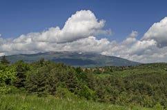 Scène de printemps avec la clairière de montagne, la forêt et le secteur résidentiel du village bulgare Plana, montagne de Plana Photographie stock libre de droits