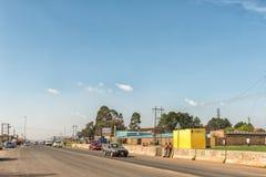 Scène de rue avec des entreprises et véhicules dans Phuthaditjhaba Images stock